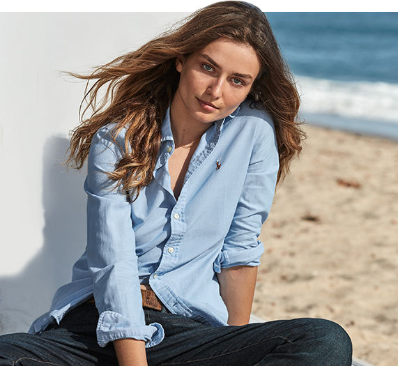 Woman wears loosely buttoned light blue oxford shirt on beach