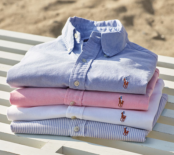 Stack of neatly folded oxford shirts in spring hues