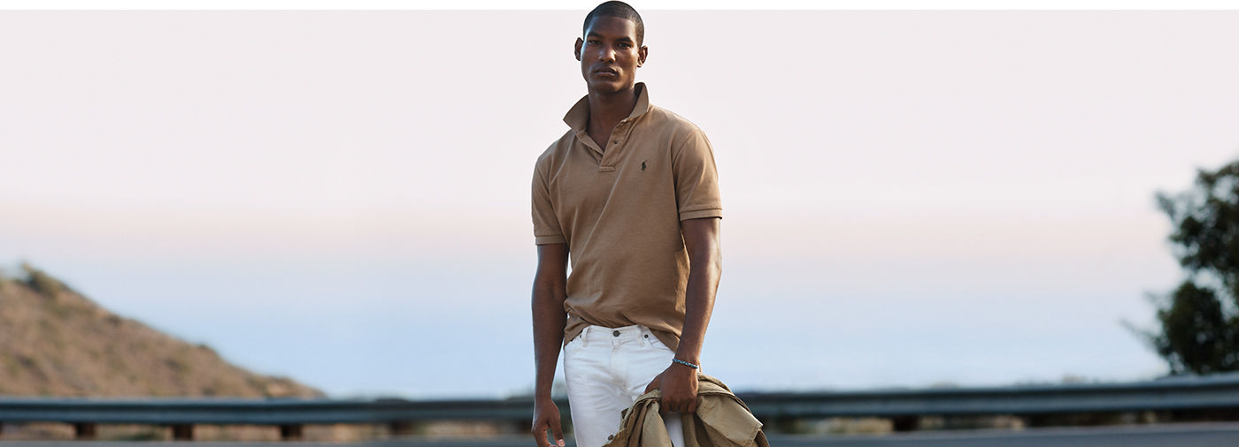 Man on bridge models khaki Pol shirt with turned-up collar