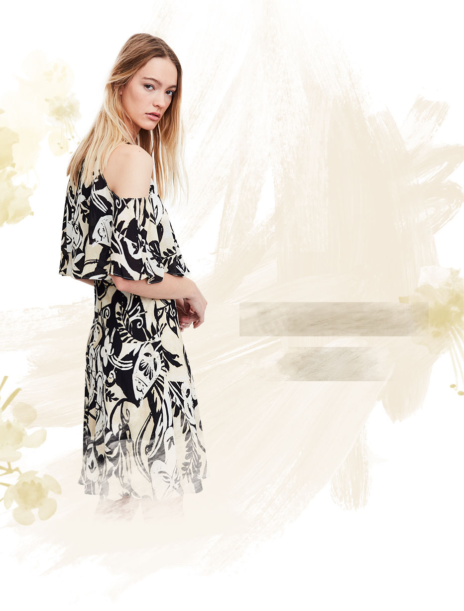 Woman in black & white abstract-print dress looks over shoulder