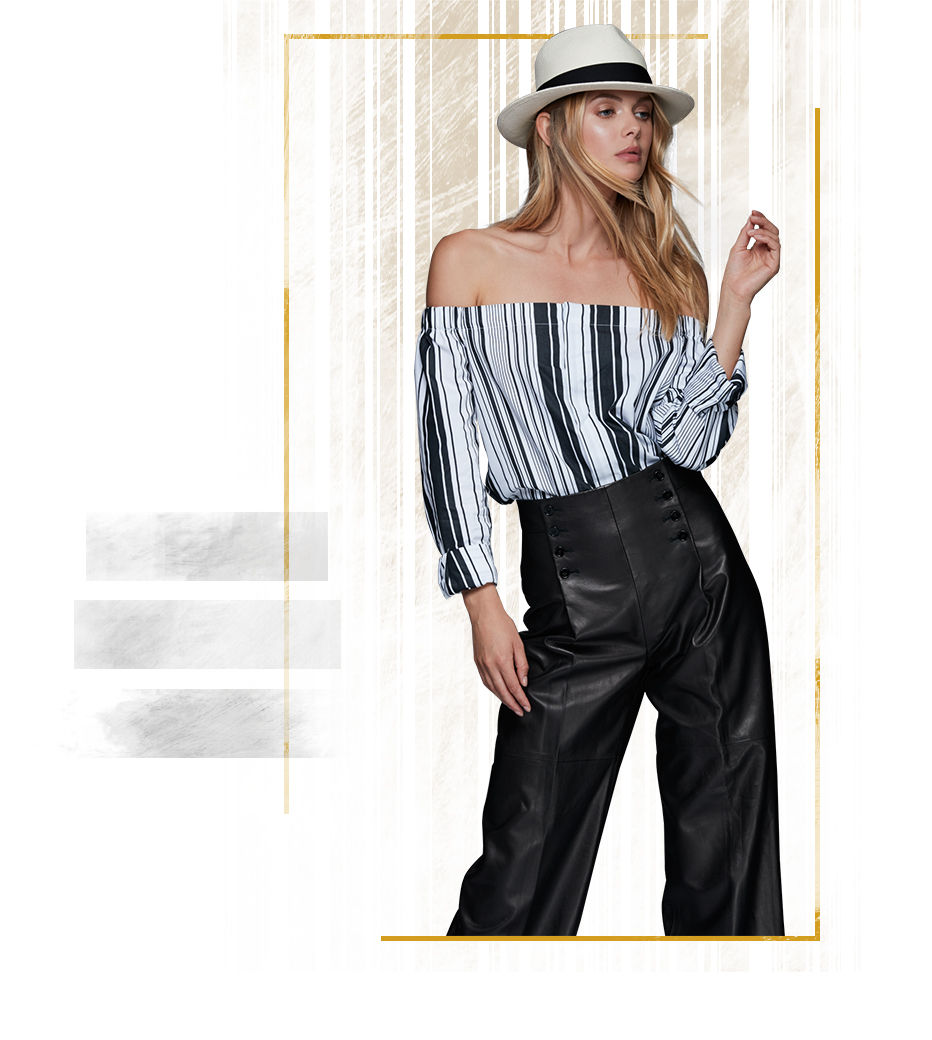 Woman wears white brimmed hat with striped blouse & leather culottes