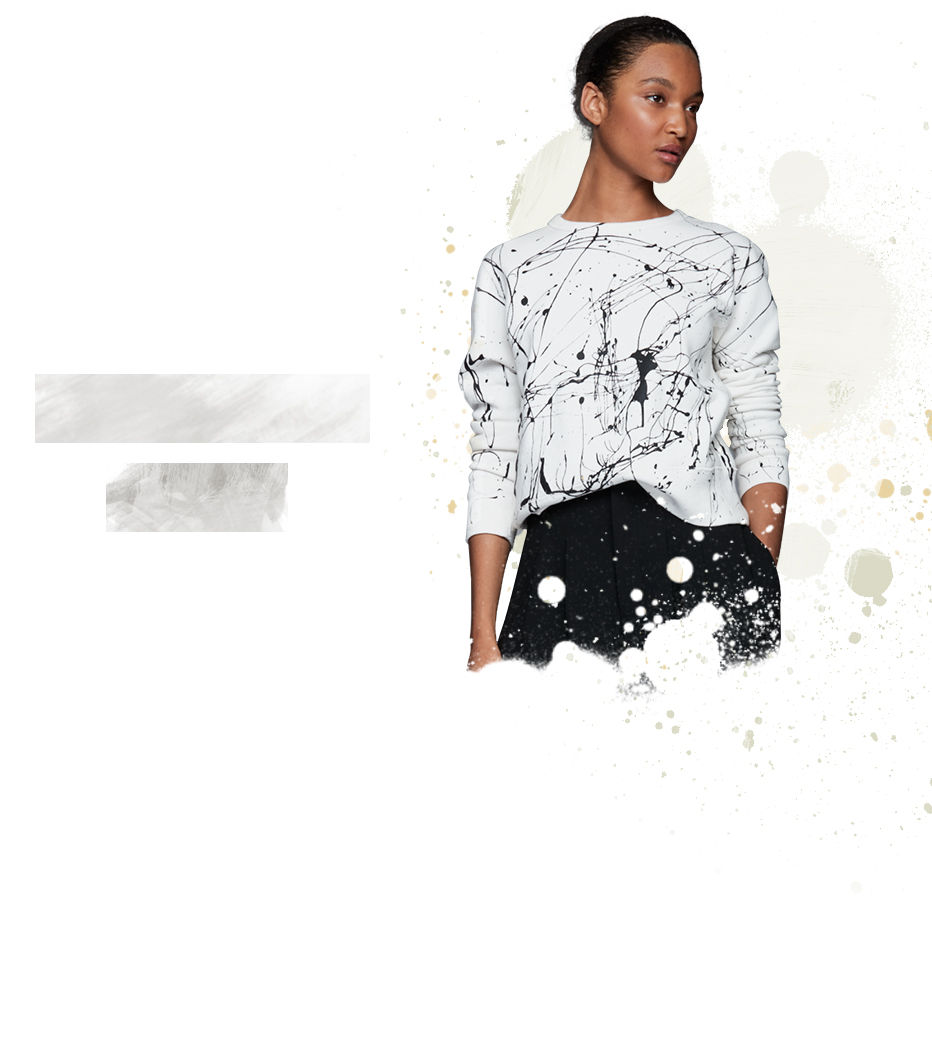 Woman models white sweatshirt accented with black paint splatters