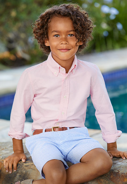 Boy models pink long-sleeve button down and blue-and-white seersucker shorts.