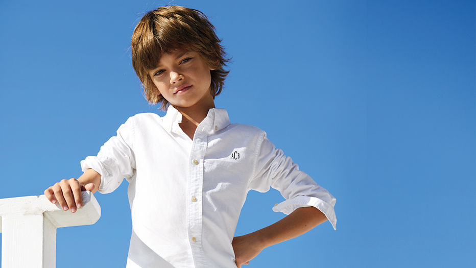 Boy poses wearing white button-down oxford with monogram at the chest.