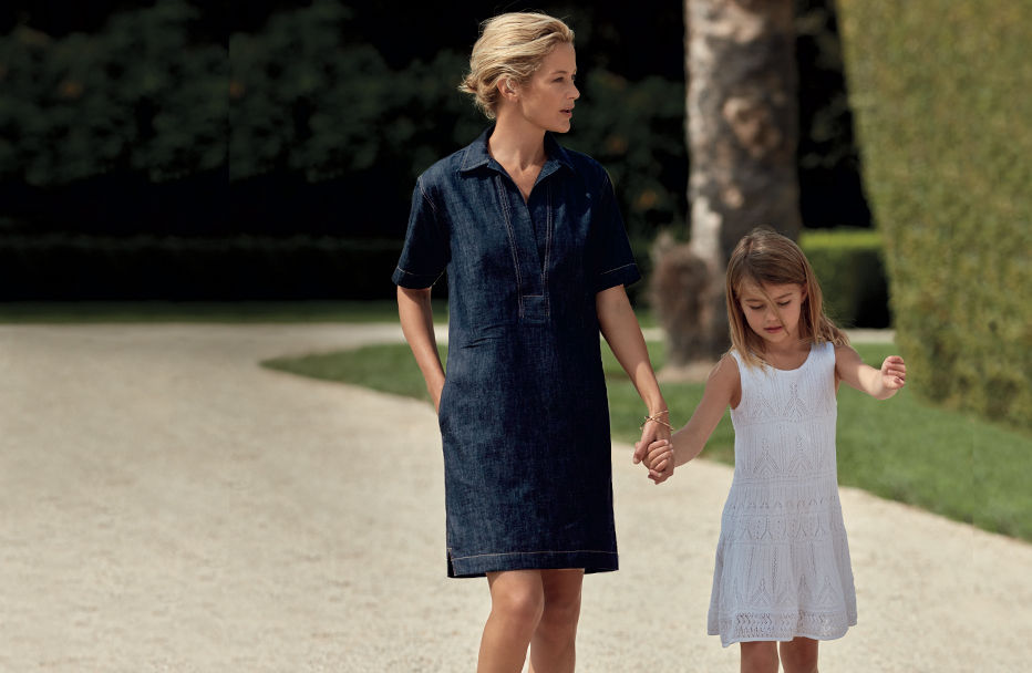 Woman in shirtdress with pockets walks down street with young girl