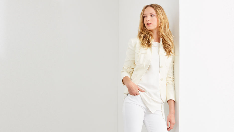 Woman models cream cardigan with white top & tonal jeans