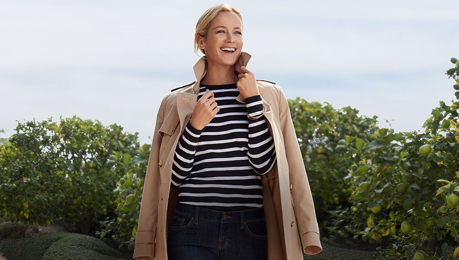 The model in striped top with tan coat draped over her shoulders