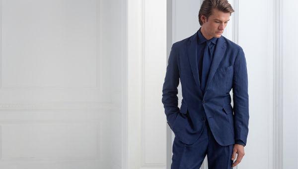 RALPH LAUREN. Man models navy sport coat, worn with navy tie, shirt \u0026 pants