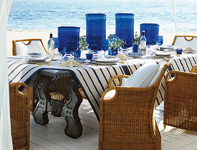 Wicker chairs and table on beach, set with striped tablecloth & blue glassware