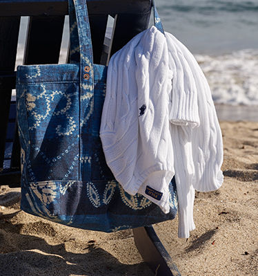 White cable-knit sweater carried in blue tote bag on beach