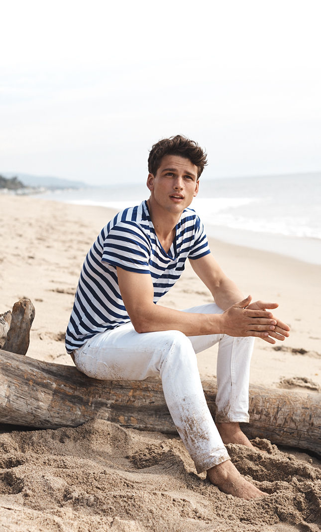 Man in striped tee & white jeans sits on beach
