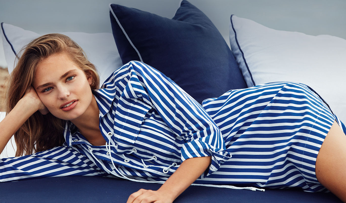 Reclining woman in blue-and-white striped shirtdress with lace-up placket