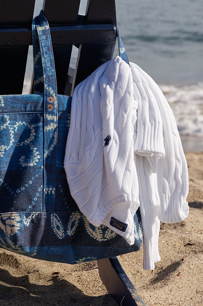 White cable sweater being carried in tote bag on beach
