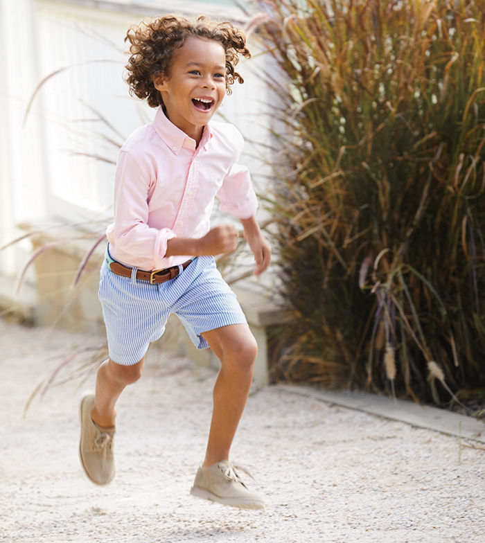 Boy runs in belted light blue dress shorts & pink button-down
