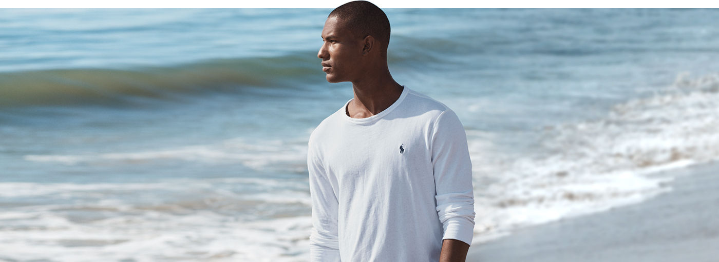 Man walks along ocean in white sweatshirt accented with Polo Pony