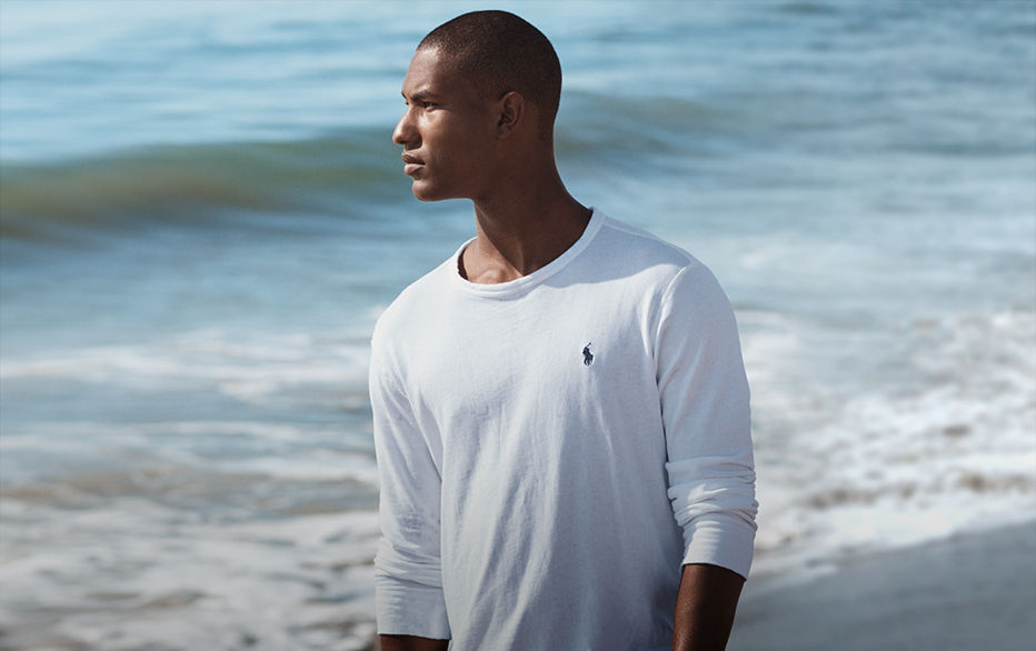 Man on beach in white sweatshirt with navy Polo Pony at chest