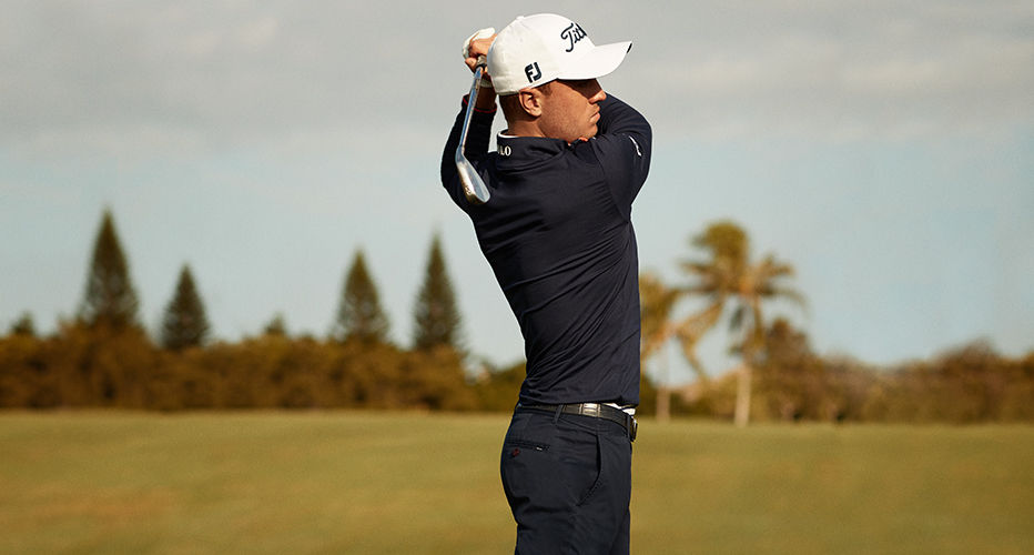 Justin Thomas on green in black pants, belt, and athletic half-zip top