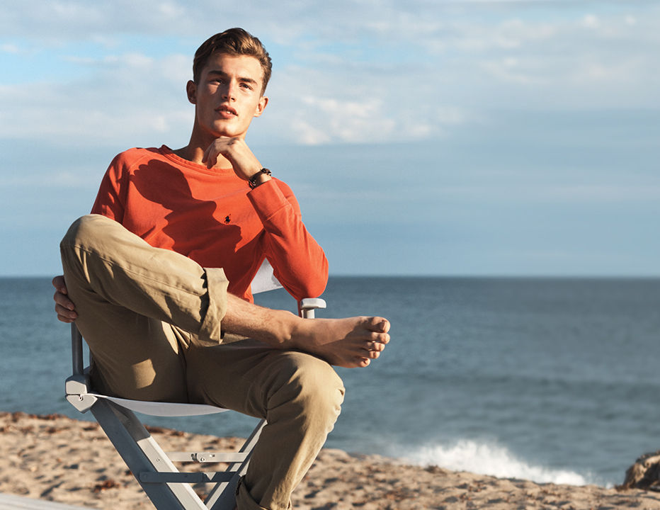 Man in faded red sweatshirt & chinos sits on sandy beach.