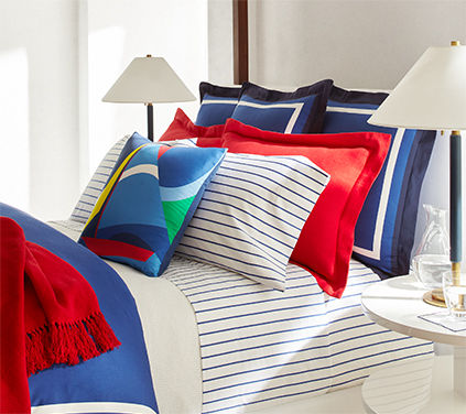Navy & white striped bedding complemented by bright throw blankets & pillows