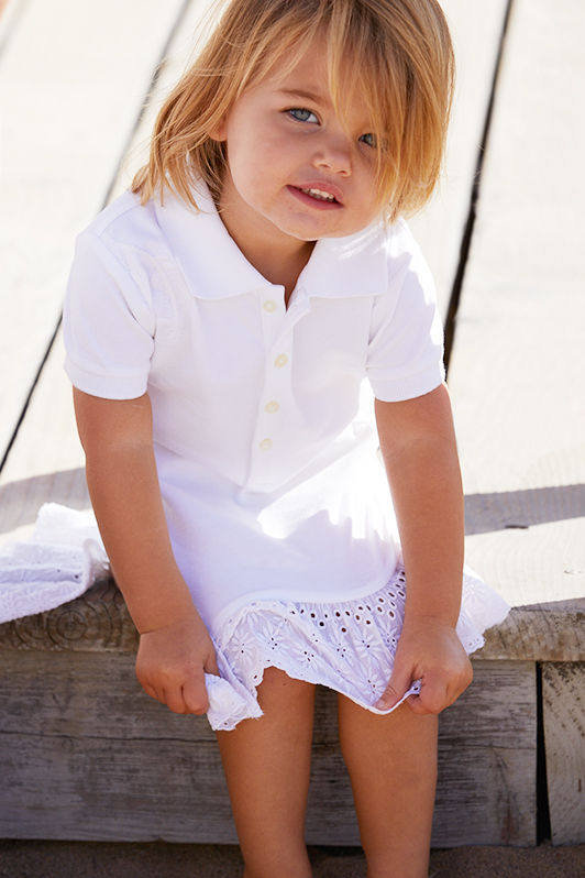Baby girl wears white Polo dress with embroidered eyelet hem.