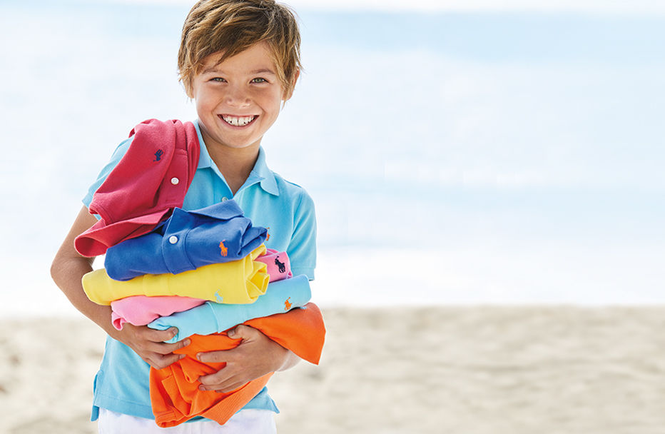 Boy wearing blue Polo holds stack of colorful Polo shirts.