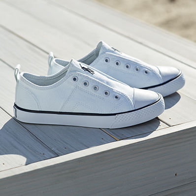 Pair of laceless white sneakers.