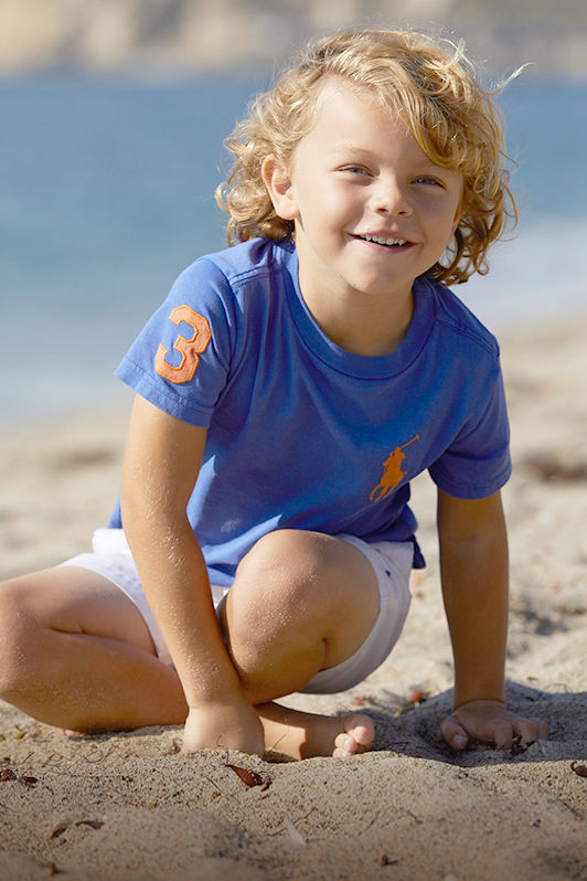 Boy on beach wears blue T-shirt with signature embroidered pony and shorts.