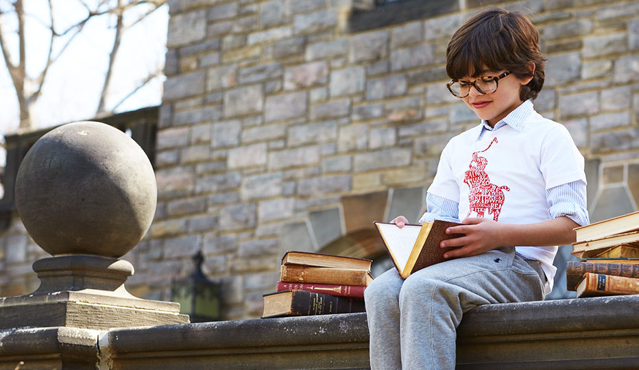 Boy reads book while wearing Polo Literacy tee and grey sweatpants.
