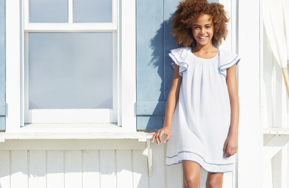 Girl wearing white flutter-sleeve dress poses in front of whitewashed house.