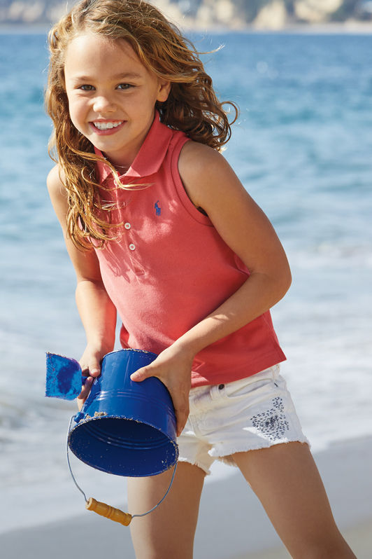Girl plays on beach while wearing sleeveless Polo shirt and white shorts.
