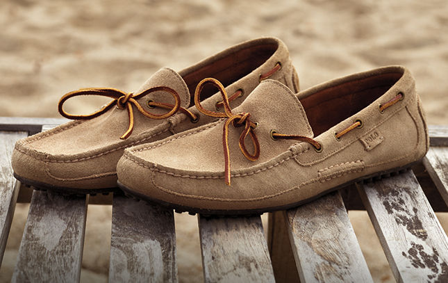 Tan suede boat shoe with leather laces that loop through the sides