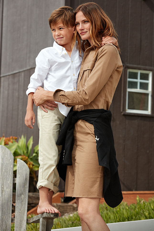 Woman in beige knee-length shirtdress stands with arms around young boy