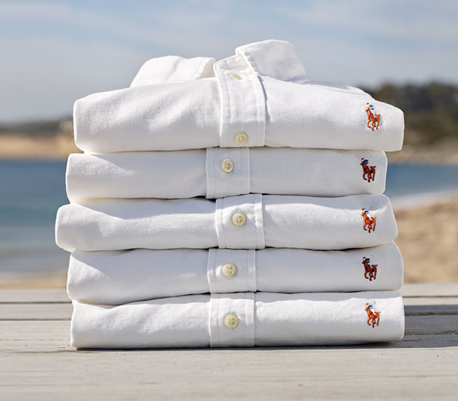 Stack of folded white oxford shirts with polo pony at chest.