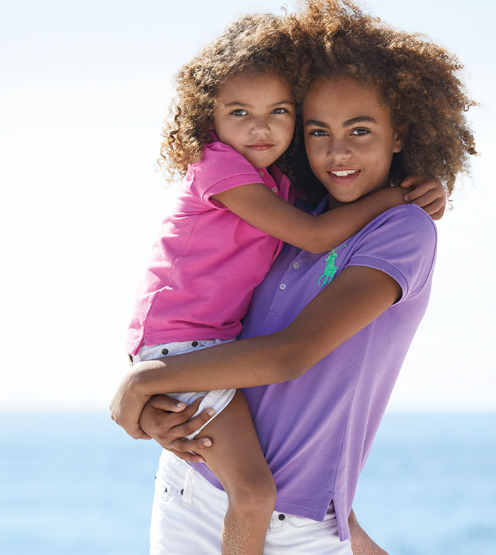 Older girl wearing purple Polo holds younger girl wearing pink Polo