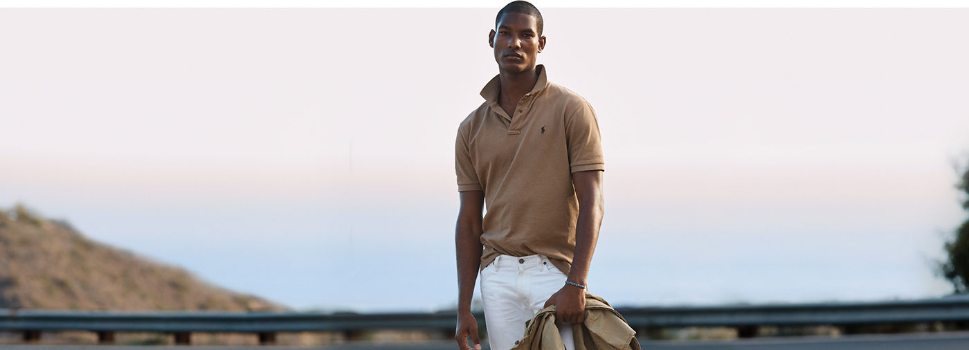 Man on bridge models khaki Polo shirt with turned-up collar