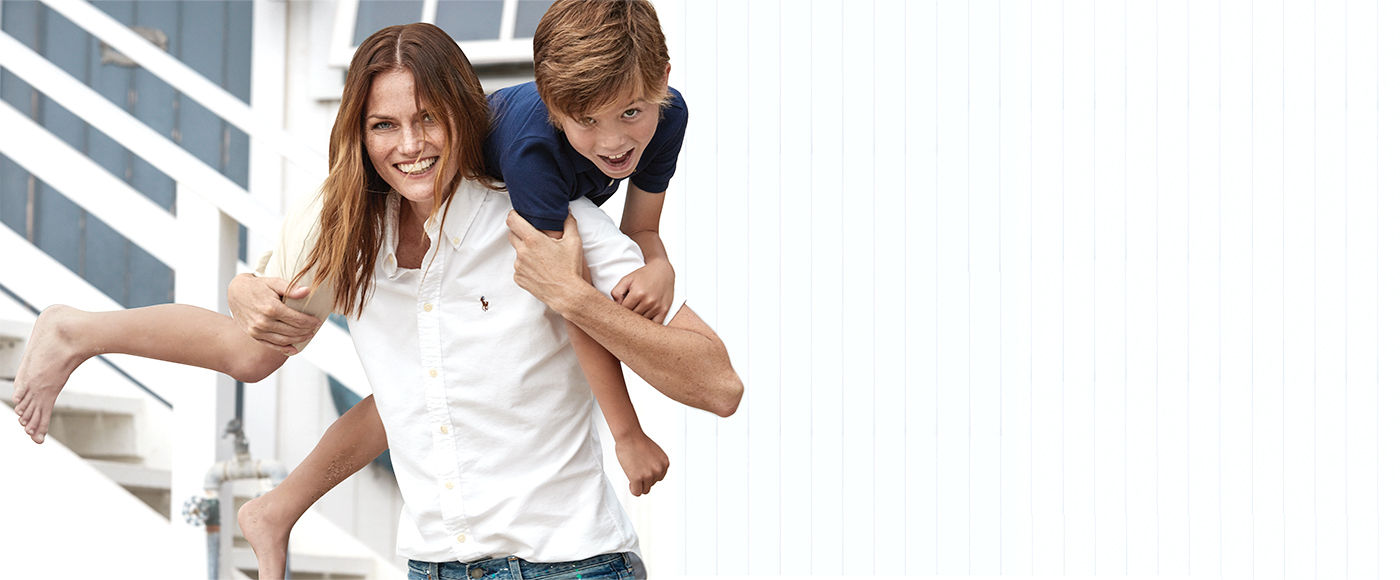 Mother in white oxford shirt with son on shoulders