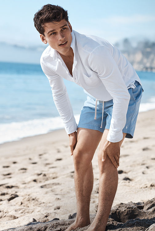 Man on beach in drawstring blue shorts