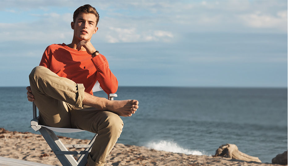 Man in faded red sweatshirt & chinos sits on sandy beach