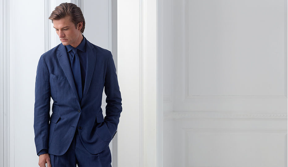Man models navy suiting with matching tie & shirt