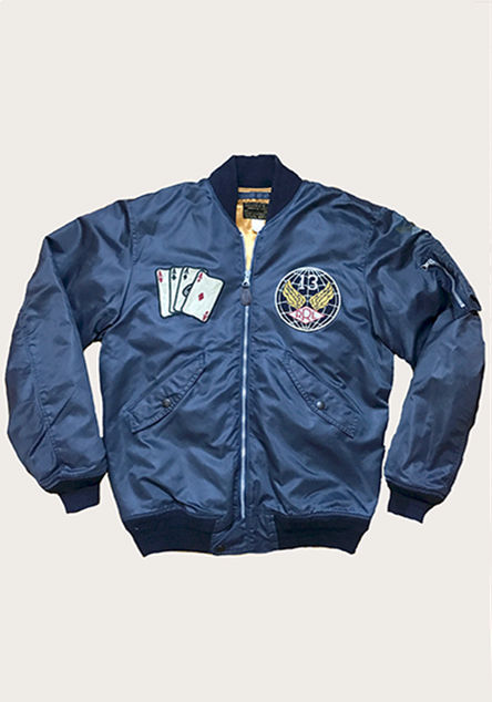 Navy bomber-style jacket with playing card patch at right chest