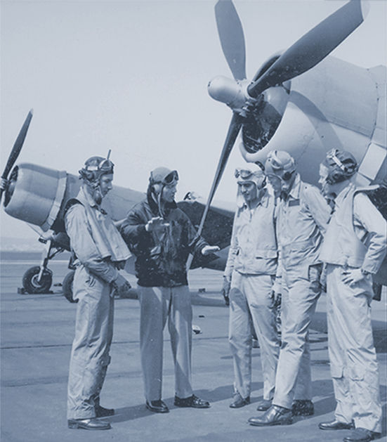 Men in flight suits have discussion near propeller planes