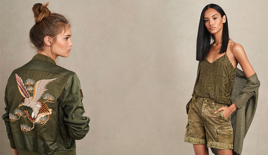 Woman in eagle-motif bomber jacket & woman in beaded army green tank