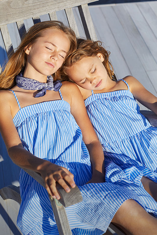 Girls wear matching blue-and-white striped tiered dresses.