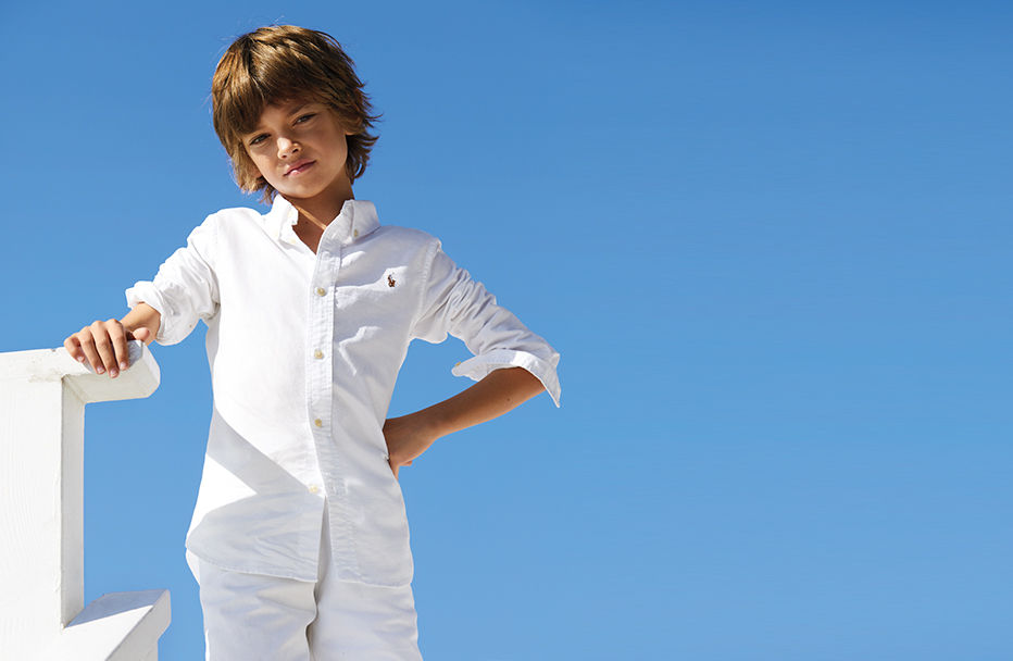 Boy wears white button-down oxford and white shorts.