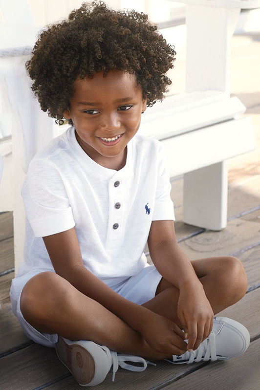 Boy models white tee with buttoned placket and white shorts.