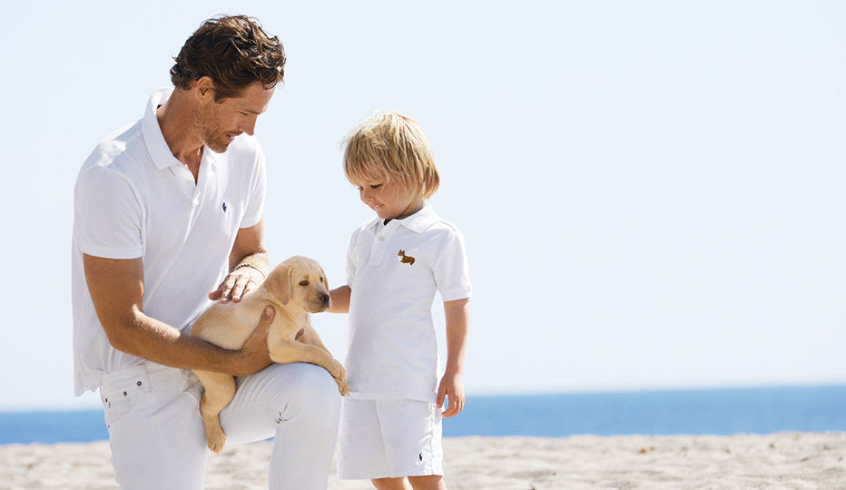 Man wears white Polo shirt and jeans on beach with boy in all-white outfit.