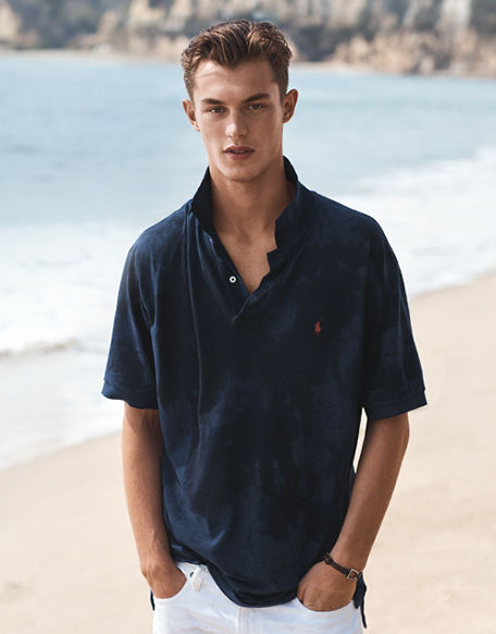 Man on beach models navy Polo shirt with white denim