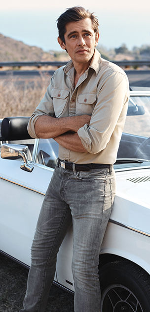 Man leans against car in Khaki shirt and skinny grey jeans