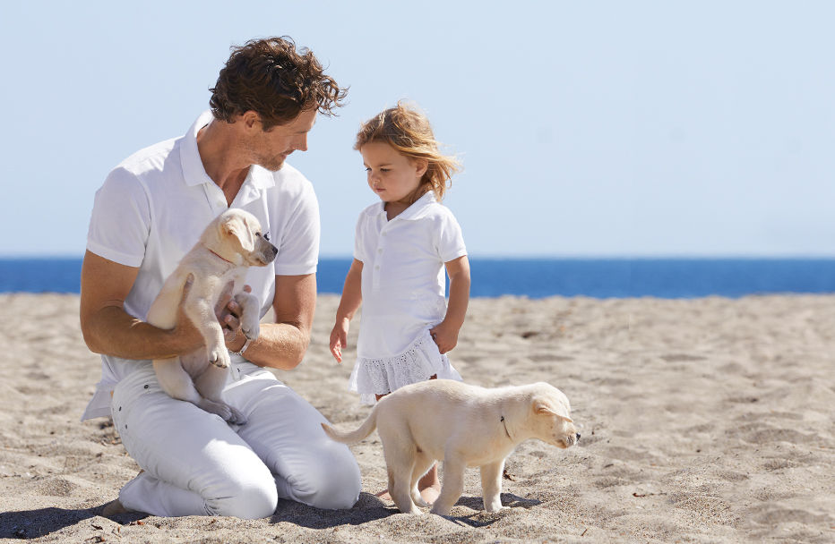 Man and child in all-white outfits play with puppies on beach.