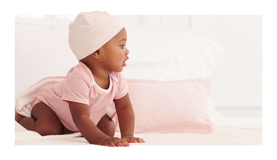 Baby crawls in pink-and-white striped bodysuit and light pink hat.